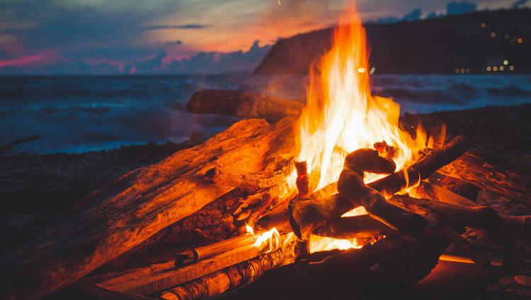 Muchas personas se reunen en la playa alrededor de una hoguera
